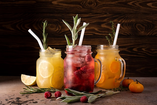Homemade fruit cocktails with fresh fruit pieces and ice in glass mugs