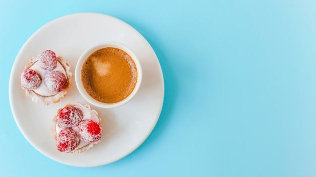 파란색 배경 위에 접시에 나무 딸기와 커피 컵으로 만든 과일 타르트