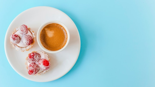 Homemade fruit tart with raspberry and coffee cup on plate over the blue background