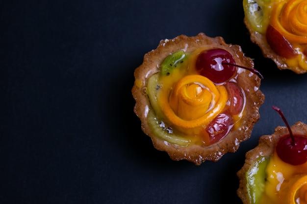 Homemade fruit tarts with orange kiwi and cherry on black