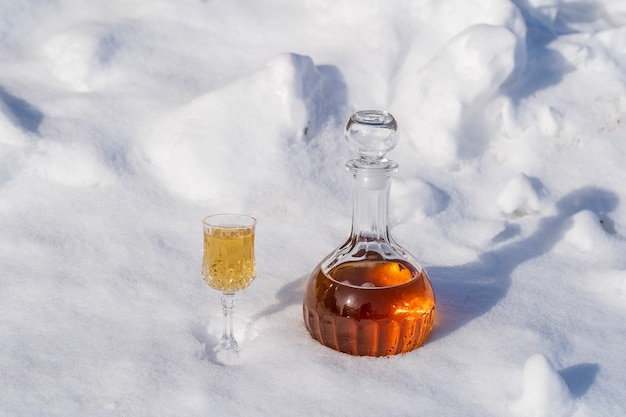 Homemade fruit tincture in a glass bottle and a wine crystal glass on a snow and white background in winter
