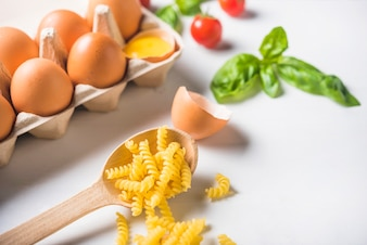 Homemade fusilli pasta with ingredients on white background