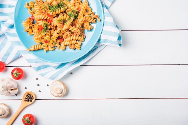 Homemade fusilli pasta with ingredients on white wooden table