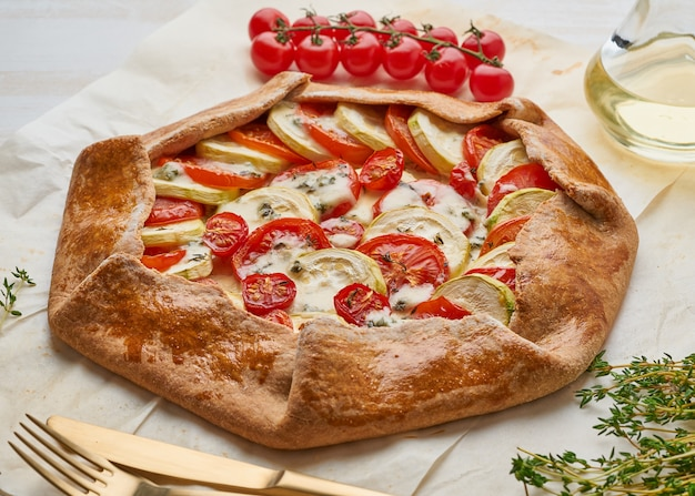 Homemade galette with vegetables, wholegrain pie with tomatoes, zucchini, cheese.