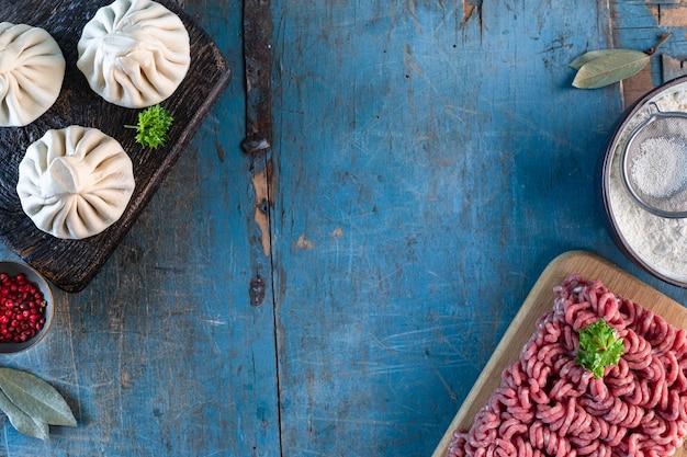 Домашние грузинские хинкали и ингредиенты для приготовления на старом деревянном синем столе. скопируйте пространство. вид сверху