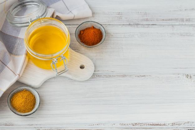 수제 버터 기름 또는 흰색 나무 테이블에 항아리 심황과 파프리카 가루에 명확히 버터.