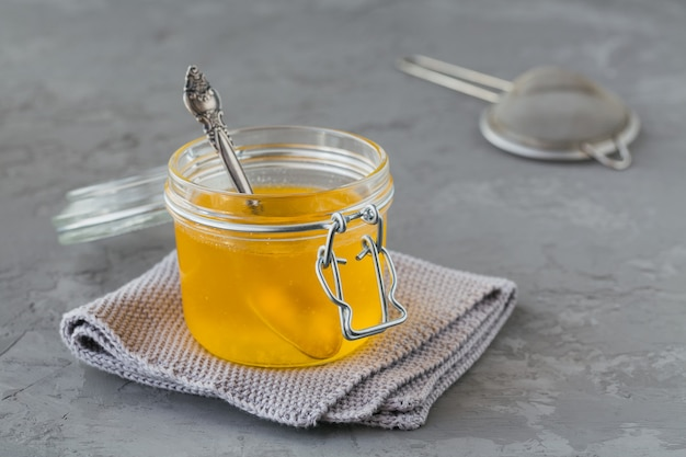 수제 버터 기름 또는 회색 콘크리트 배경에 항아리에 버터를 명확히