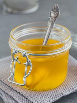 회색 콘크리트 테이블에 항아리에 직접 만든 버터 기름 또는 정화 버터