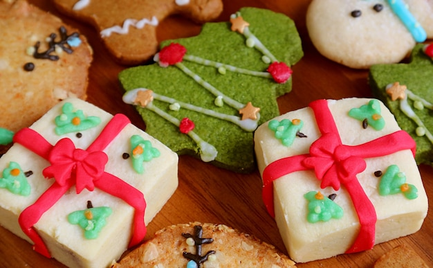Homemade gift box shaped christmas cookies with blurry xmas tree cookie on wooden background