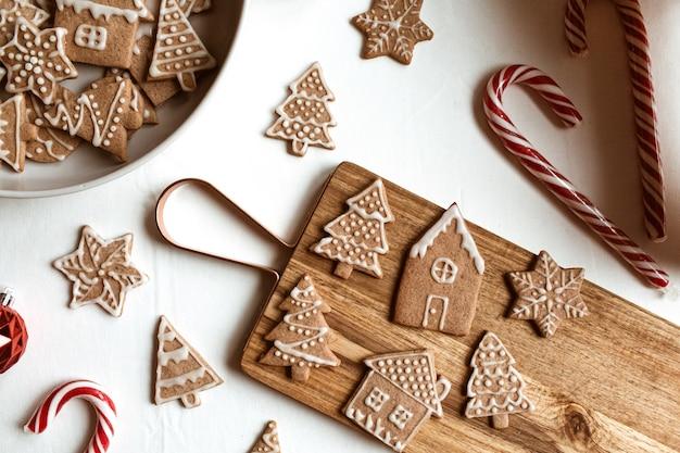 Самодельные звезды имбирного печенья, ели, дома на деревянной разделочной доске, конфеты палочки на белом. плоская планировка, вид сверху рождественский состав.