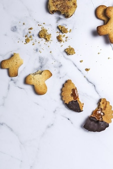 Homemade gingerbread, cinnamon and chocolate cookies on marble background from above. flat lay