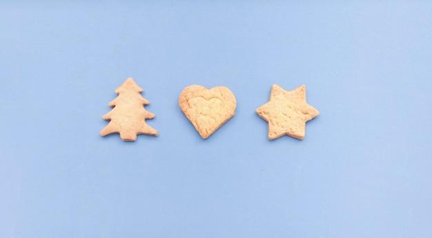 파란색 배경에 격리된 다양한 모양의 홈메이드 진저브레드 쿠키입니다. 원형 모양으로 표시되는 크리스마스 쿠키와 함께 평평하게 놓여 있습니다.