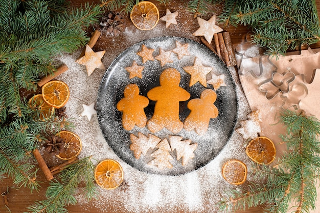 Homemade gingerbread cookies stars and christmas trees, little men decorated with powdered sugar and surrounded by spruce branches and dried oranges, cinnamon.