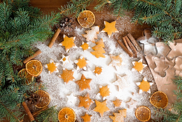 Homemade gingerbread cookies stars, decorated with powdered sugar and surrounded by spruce branches and dried oranges, cinnamon.