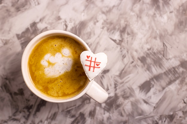 Homemade gingerbread heart-shaped cookies with a tic-tac-toe game on a cappuccino cup