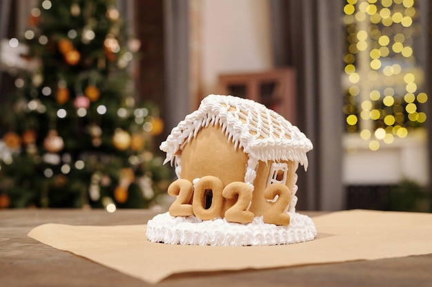 내년의 휘핑 크림과 구운 숫자로 장식 된 수제 진저 브레드 하우스