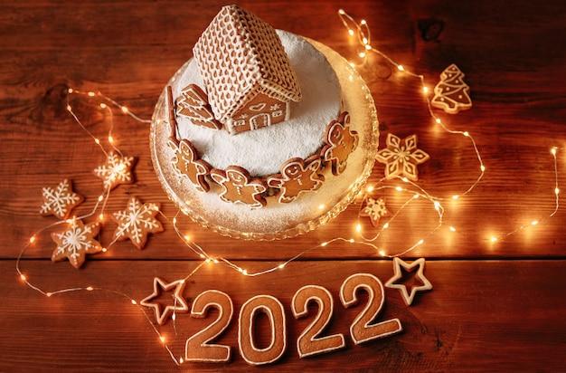 クリスマスの自家製ジンジャーブレッドハウスは、新年の数で背景を飾った