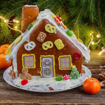 Самодельный пряничный домик с мандаринами и рождественскими огнями на деревянном столе