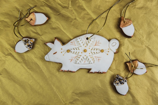 A homemade gingerbread pig covered with white icing and snowflakes on the golden