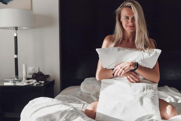 Самодельная девочка в постели утром накрывается подушкой в лучах утреннего солнца