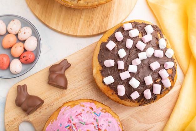 白いコンクリートの表面と黄色の織物にチョコレートの卵とウサギが付いた自家製の艶をかけられ装飾されたイースターパイ