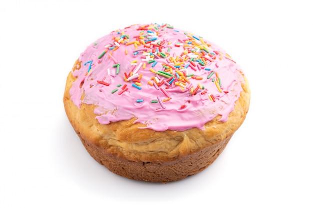 Домодельный застекленный и украшенный розовый пирог пасхи изолированный на белой предпосылке. вид сбоку.