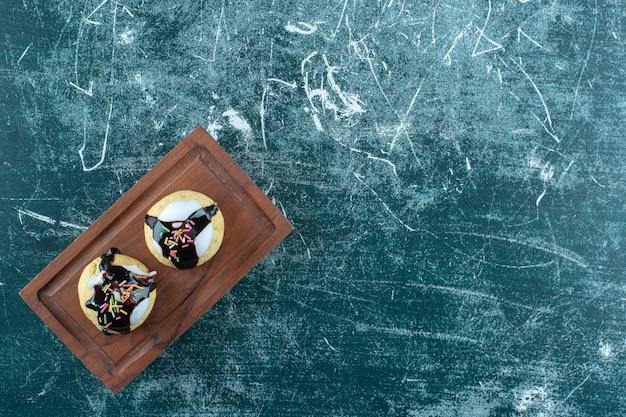Домашнее глазированное печенье на деревянной тарелке, на синем фоне. фото высокого качества