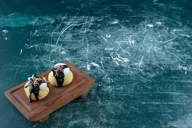 Домашнее глазированное печенье на деревянной тарелке, на синем столе.