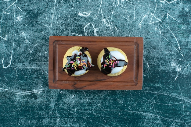 Homemade glazed cookies on a wooden plate plate, on the blue background. high quality photo