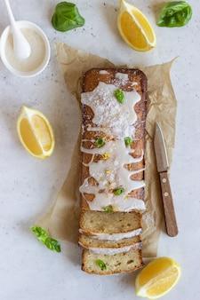Homemade glazed lemon loaf cake decorated with lemon zest, basil and coconut chips.