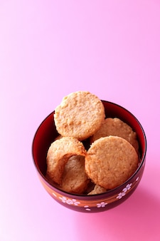 Homemade gluten free oatmeal cookies in bowl. selective focus. pink background.