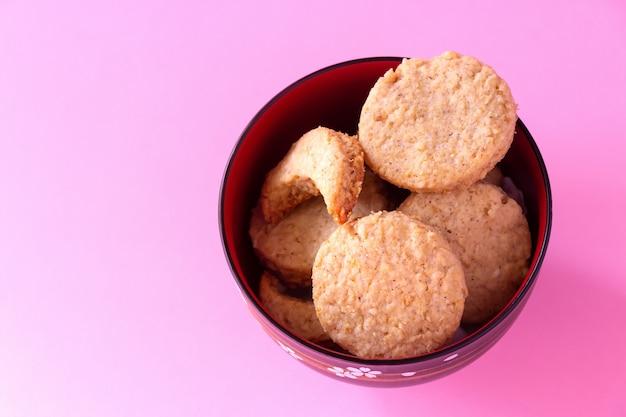 그릇에 만든 글루텐 무료 오트밀 쿠키. 선택적 초점. 분홍색 배경입니다.