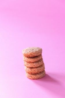 Homemade gluten free oatmeal cookies. selective focus. pink background.