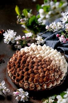 Домашний традиционный итальянский десерт тирамису без глютена, посыпанный какао-порошком, украшенный цветущей яблоней, синей тканевой салфеткой и кофейными зернами на темном фоне текстуры.