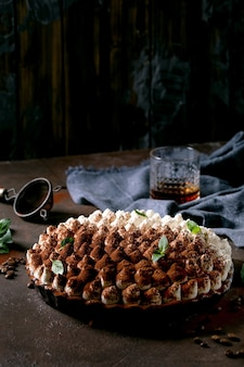 暗いテクスチャーの表面に、ミントの葉、グラス 1 杯のウィスキー、青い布ナプキン、コーヒー豆で飾られたココア パウダーをまぶした自家製のグルテン フリー ティラミスの伝統的なイタリアのデザート。