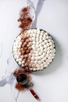 흰색 대리석 표면에 코코아 가루를 뿌린 수제 글루텐 프리 티라미수 전통 이탈리아 디저트. 평면도, 평면 누워. 공간 복사