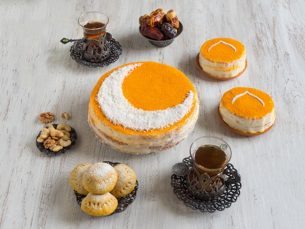 三日月の自家製ゴールデンケーキ。ティーカップと日付が添えられています。ラマダンの壁