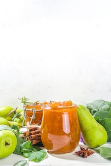 Homemade golden colored pear jam, with farm pears and leaves on white wooden background copy space