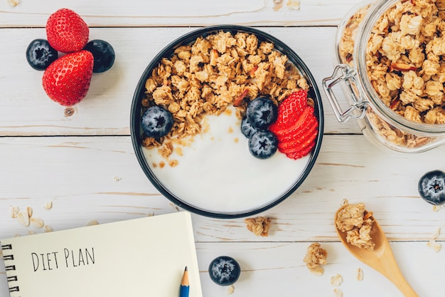 Homemade granola and fresh berries on wood table with note book and text diet plan concept, copy space.