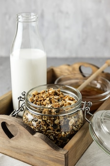 Homemade granola in a glass jar and a bottle of milk and honey.