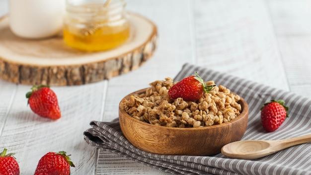 Самодельная мюсли в деревянной миске с клубникой на деревянных фоне. концепция здорового завтрака. copyspace.