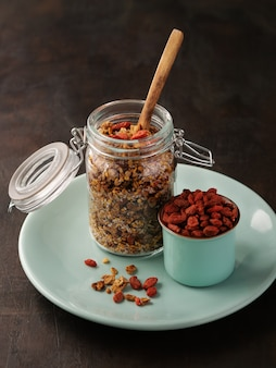 Homemade granola , muesli in open glass jar with goji berries and fresh bee pollen.