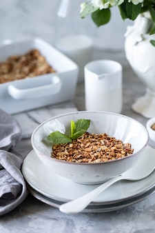 Homemade granola in white plate. healthy breakfast with granola, yogurt, fruits, berries on a white plate in a white plate.