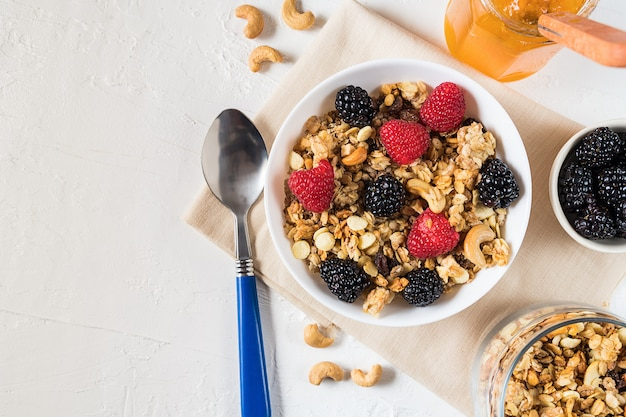 Homemade granola with fresh berries and cashew nuts on white background flat lay.