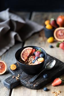 新鮮なベリーと自家製グラノーラ、朝食のフルーツ。健康的な食事のコンセプトです。木製のテーブル。暗い背景