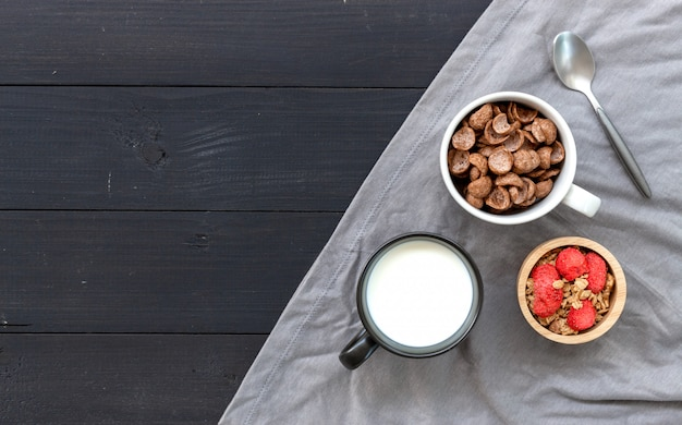 Homemade granola with milk for breakfast on wooden table.