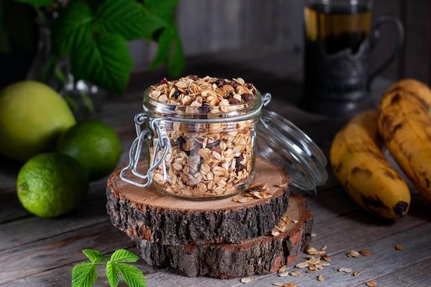 ヘルシーな朝食のためのガラスの瓶にナッツ、レーズン、種子を入れた自家製グラノーラ。ヘルシービーガンスナック