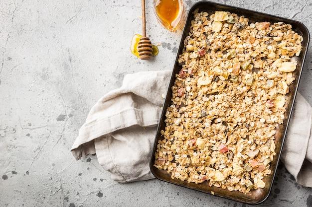 ベーキングトレイにオート麦、蜂蜜、ナッツを入れた自家製グラノーラ