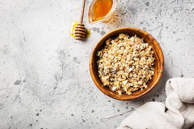 ボウルにオーツ麦、蜂蜜、ナッツを入れた自家製グラノーラ