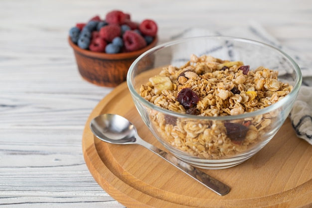Homemade granola with raisins, nuts and berries in a glass bowl